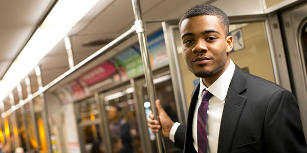 A male student wearing a suit and standing on a subway train.