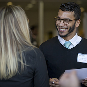 A man smiles while meeting an employer.