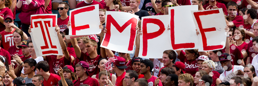 Temple fans at a sports event with a Temple sign.