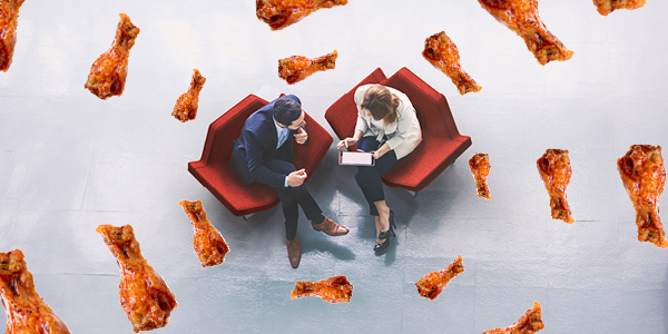 Two professionals meeting with chicken wings surrounding them..