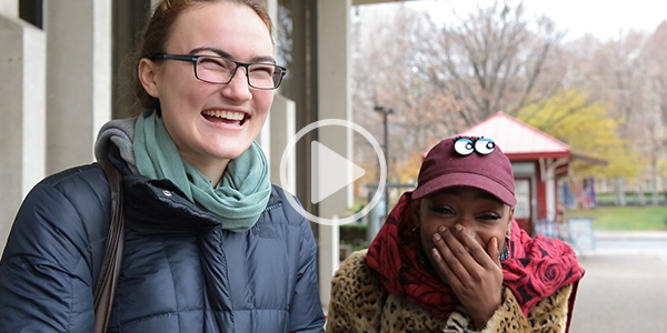 Two girls laughing with a play button to indicate a video.