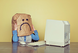 Kid at Desk with Paper Bag over Head