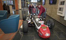 Two students pushing the Temple Formula One car through the engineering building.