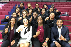 """The women's basketball team sitting together on bleachers holding up their index fingers to show """"No. 1."""""""