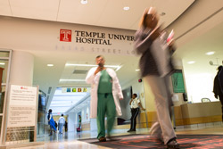 People walking through the entrance to Temple University