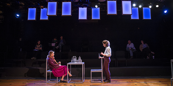 Two women on stage acting while five people watch and take notes.