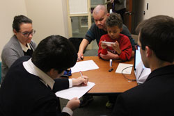 A man and his son reviewing documents with attorneys at a table.