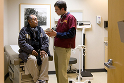 A patient sitting on an examination table listening to a doctor.