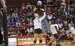 One volleyball player setting the ball up for another player.
