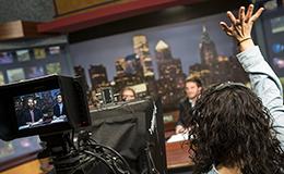 Students in a TV studio preparing to shoot a news segment.