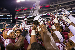 Temple's football team holding the AAC Conference Division title trophy.