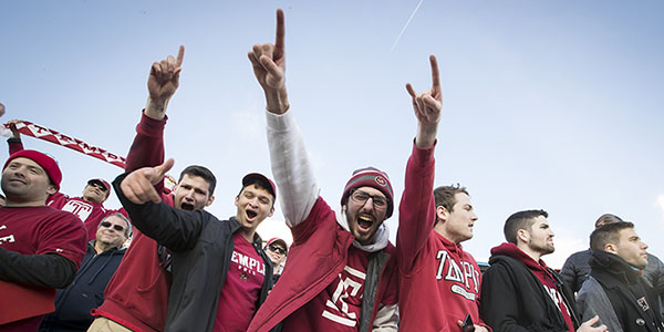 A group of students cheering at a Temple football game.