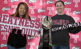Students posing with the American Athletic Conference championship trophy.