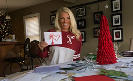 Alison Boettlin holding a holiday card next to a table covered with holiday cards and decorations.