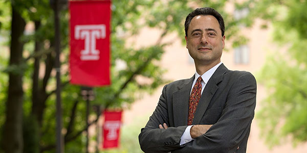 Gregory Mandel standing near trees and a Temple flag with his arms crossed.