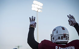 A Temple football player holding his arms up and looking to the sky.