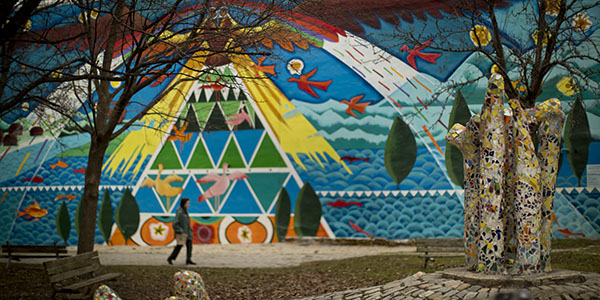 A colorful mural with birds and fish next to a park with mosaic artwork.