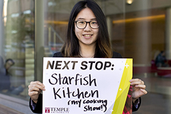 "Lei Zhao holding a sign that says ""Starfish Kitchen (my cooking show!)""."