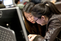 Two women working together on a computer.