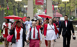 A group of people wearing cherry and white walking on campus.