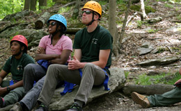 Three people wearing helmets and sitting on a rock in the forest.