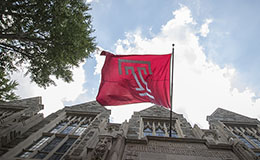 A Temple flag hanging above Sullivan Hall with a blue sky and tree in the background.