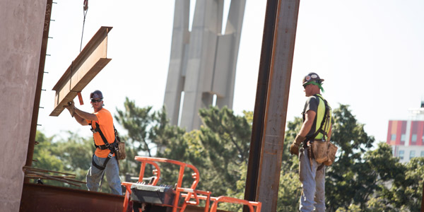 Construction workers laying a beam at the site of Temple's new library.