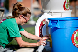 Kathleen Grady spray-paints a house number onto a recycling bin