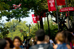 Students walking on campus under Temple 'T' flags