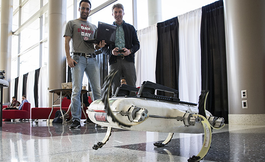 Two men operating a robot as it moves across the floor.