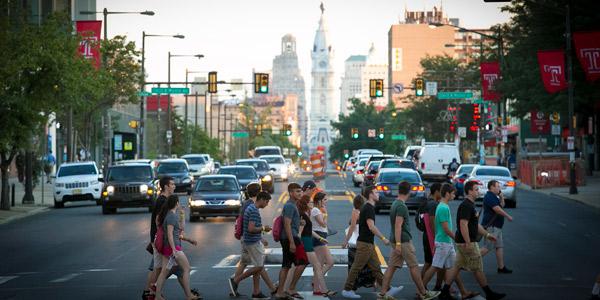 Students walking across Broad Street on campus.