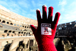a red glove with the Temple 'T' on it in front of the Colosseum.