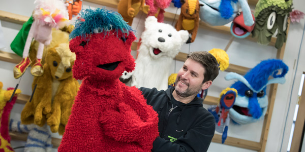Michael Latini playing with a furry red puppet.