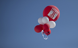 Cherry and white balloons floating in the air.