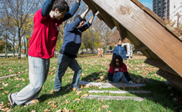 Temple alumni lifting a wooden pallet in an open lot.