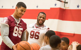 Temple football players Dan Archibong and Hez Trahan playing basketball with kids.
