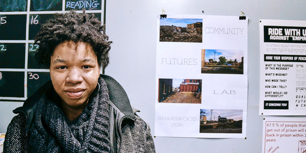 Rasheedah Phillips standing in front of Community Futures Lab poster.