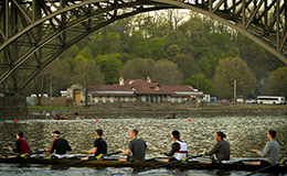 The men's rowing team on the water with the boathouse under construction in the background.