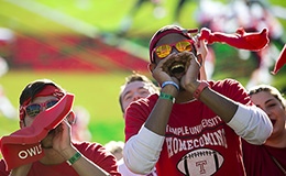 Two students cheering at a football game.