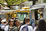 A crowd of people in front of a row of food trucks on campus.