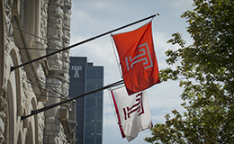 Two Temple flags with Morgan Hall in the background.