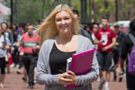 A blond woman holding books on Liacouras Walk