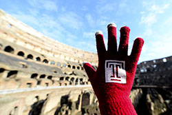 A hand wearing a Temple glove in front of the Colosseum in Rome.
