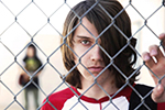 A boy from the documentary 'The Bad Kids' holding a chain link fence.
