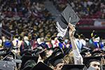 A graduate triumphantly raising his cap at commencement.