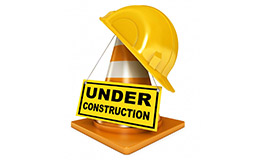 A yellow hardhat on top of a traffic cone with an under construction sign.