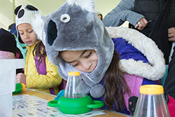 A young girl looking through a magnifying glass at EarthFest 2015.