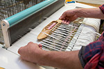 A person working with white fabric on a loom.