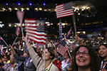 Attendees waving American flags in the crowd of the 2008 DNC.