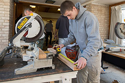 A student using a saw to build the Philadelphia Flower Show exhibit.